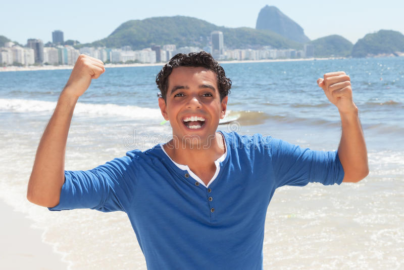Cheering latin guy at Copacabana beach at Rio de Janeiro royalty free stock image