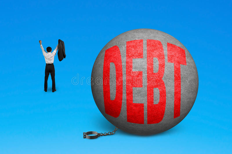 Cheering man free from debt ball shackle. Isolated on blue stock photo