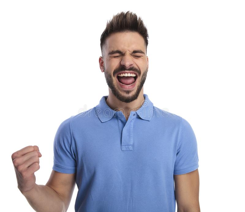 Cheering man wearing a light blue polo feeling excited. Shouting out loud and holding his fist tight, on a light background stock photo