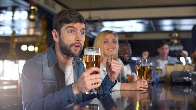 Cheering masculino ansioso para a equipe e guardando o vidro de cerveja, equipe favorita de apoio fotografia de stock royalty free