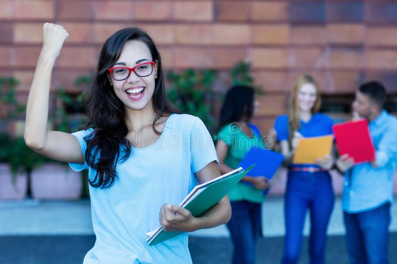 Cheering nerdy french female student with group of students stock images