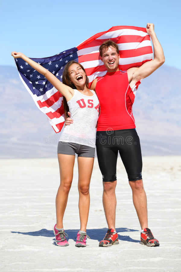 Cheering people athletes holding american USA flag. Celebrating happy with winning gesture after running. Young multicultural fitness runner couple in excited royalty free stock photo