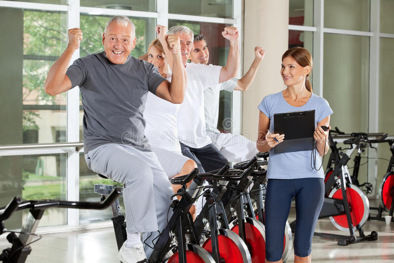 Cheering senior citizens. Cheering happy senior citizens with fitness trainer in gym royalty free stock images