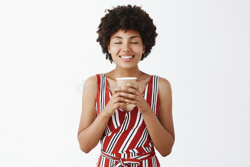 Cheering smell of coffee, adore this drink. Pleased and cute African American young woman with curly hairstyle, holding stock photography
