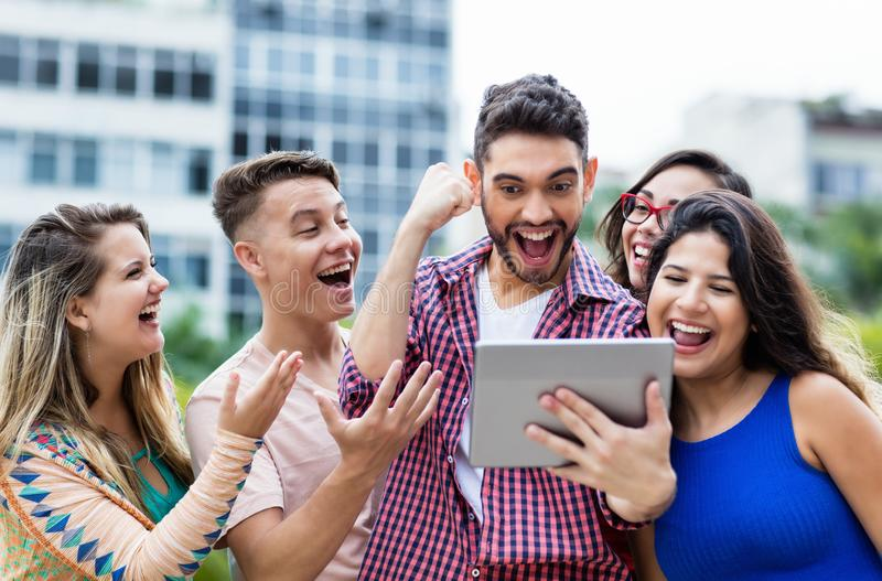Cheering spanish hipster student with tablet computer and group of cheering international students royalty free stock images