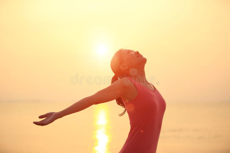 Cheering woman open arms on beach. Cheering woman open arms on sunrise / sunset beach royalty free stock images