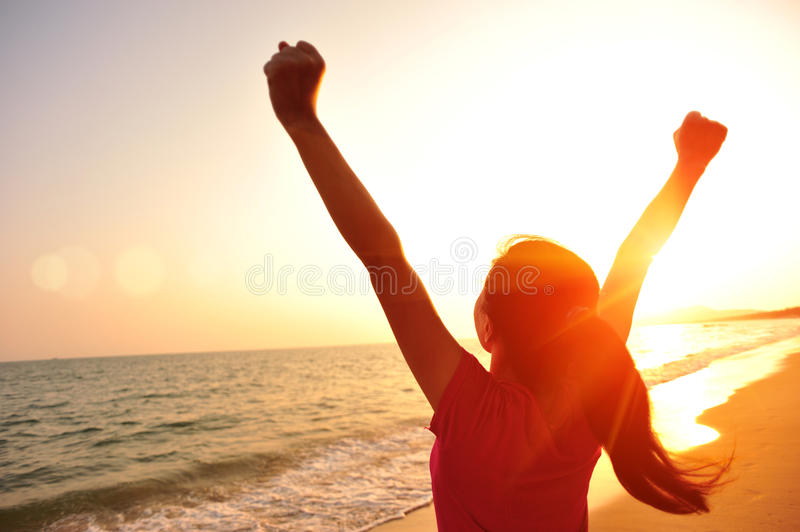 Cheering woman open arms to sunrise at sea royalty free stock image