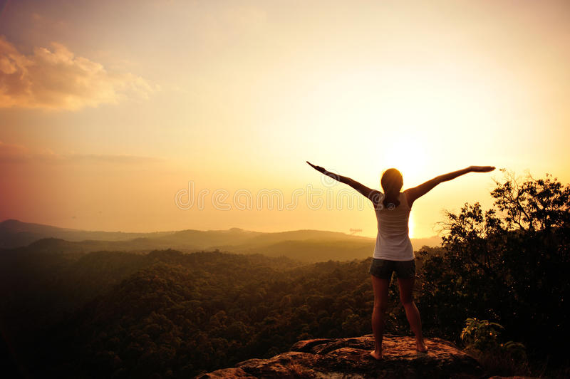 Cheering woman open arms on top hill. Cheering woman open arms on sunrise / sunset mountain peak stock images