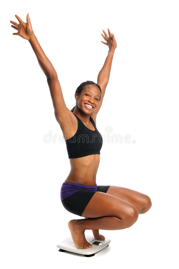 Cheering Woman on Scale. African American woman cheering on scale isolated over white background royalty free stock photos