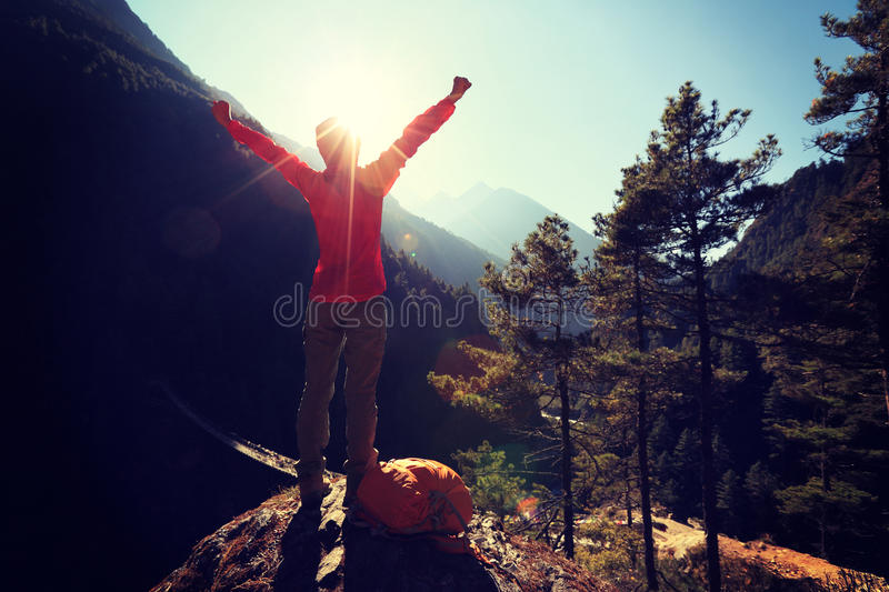 Cheering young woman hiker open arms to the sunrise royalty free stock photo