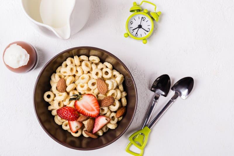 Cheerios, bayas y huevo enteros de los anillos del grano del desayuno tradicional equilibrado en la tabla blanca fotos de archivo