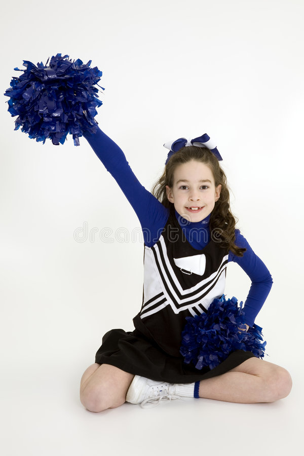 Nine year old Caucasian girl dressed in a blue cheerleader outfit royalty free stock photo