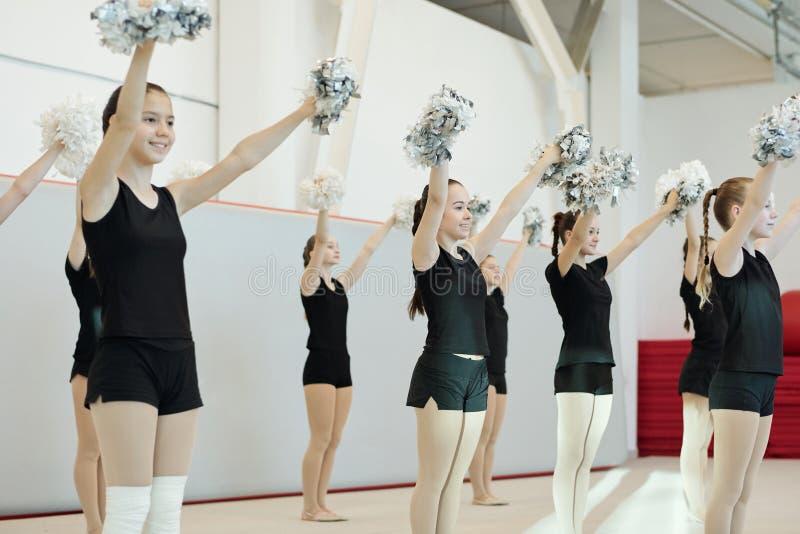cheerleader adolescenti che esaltano pomponi fotografie stock