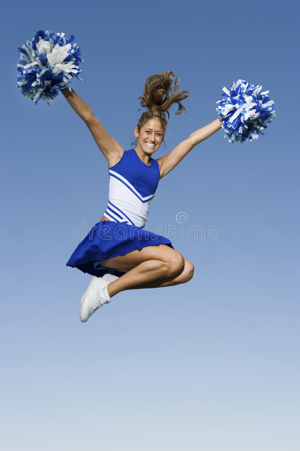 Cheerleader Jumping With Pom-Poms stock photography