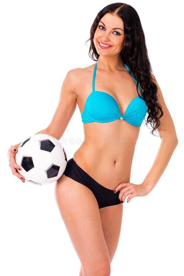 Cheerleader, mit einem Fußball, junge sexy Brunettefrau im Bi stockfotografie