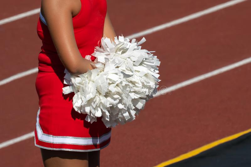 Cheerleader with Pom Poms. On sideline of an American football game - Ready to Cheer on the team stock photo