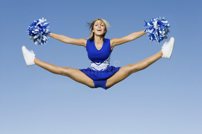 Cheerleader-With Pompoms Doing-Spalten gegen Himmel lizenzfreies stockbild