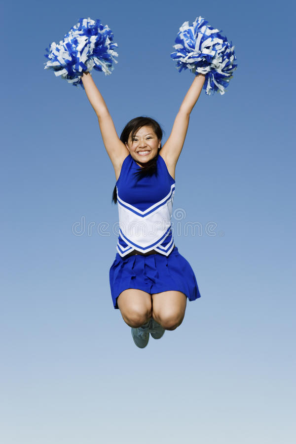 Cheerleader With Pompoms In Midair Against Sky stock photos