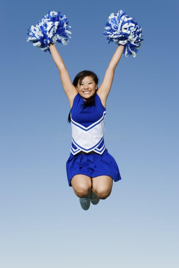 Cheerleader-With Pompoms In-mitten in der Luft gegen Himmel stockfotos