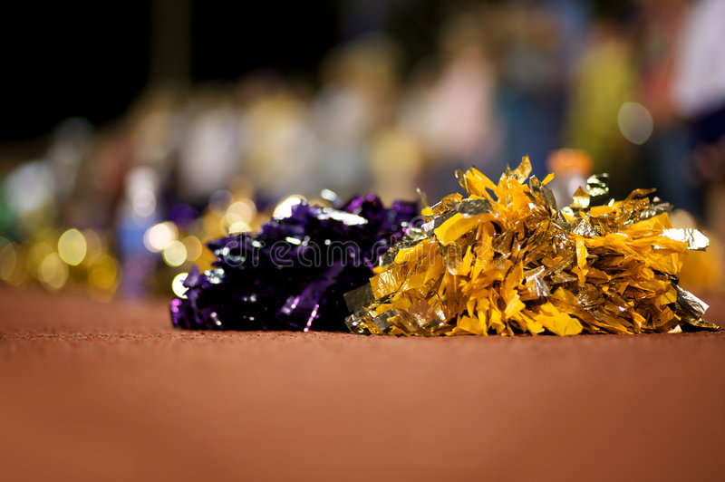 Cheerleader Poms. A close up of cheerleader poms on the ground with the crowd in the background out of focus - narrow DOF stock photography