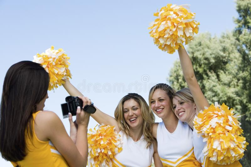 Cheerleader video taping friends royalty free stock photos