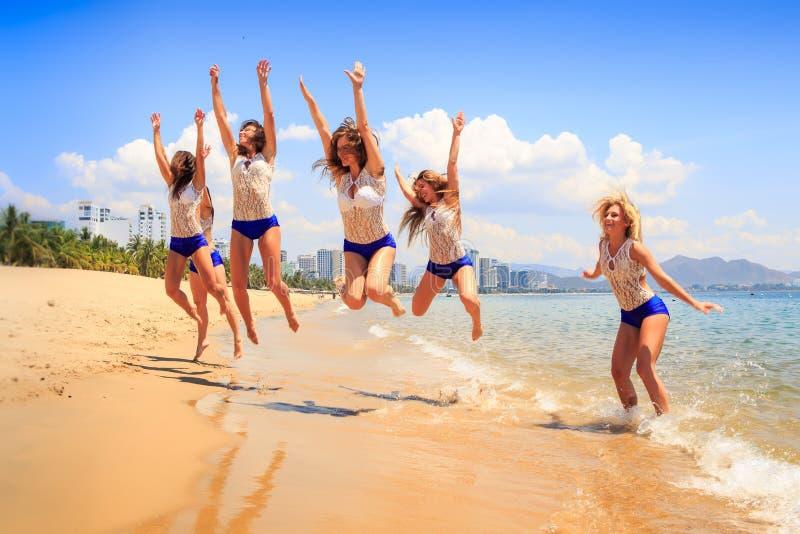 Cheerleadern springen über seichtes Wasser und Lächeln stockbilder