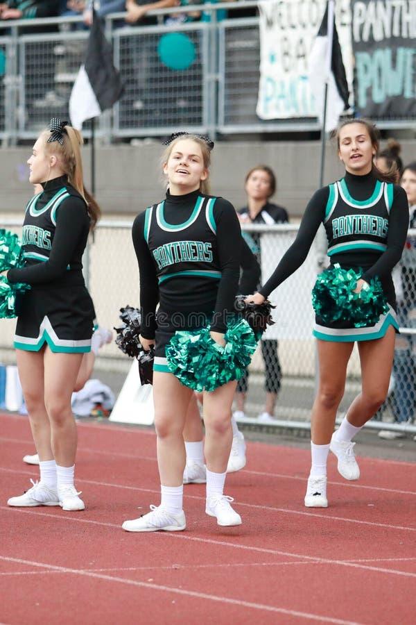 Cheerleaders bij een Spel van de Middelbare schoolvoetbal stock foto