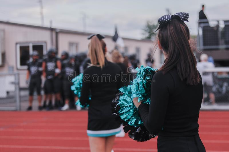 Cheerleaders bij het spel van de middelbare schoolvoetbal royalty-vrije stock fotografie