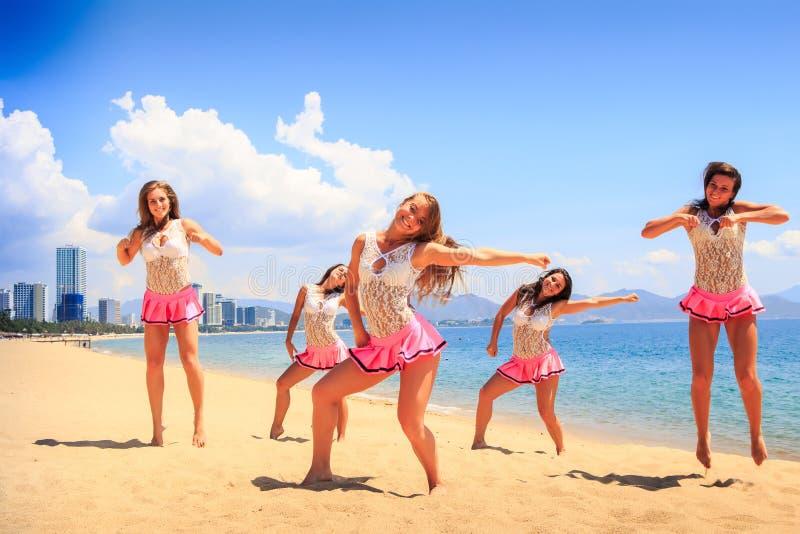 Cheerleaders in dance pose hands aside on beach against sea stock image