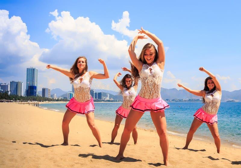 Cheerleaders in dance pose hands over head on beach against sea stock image