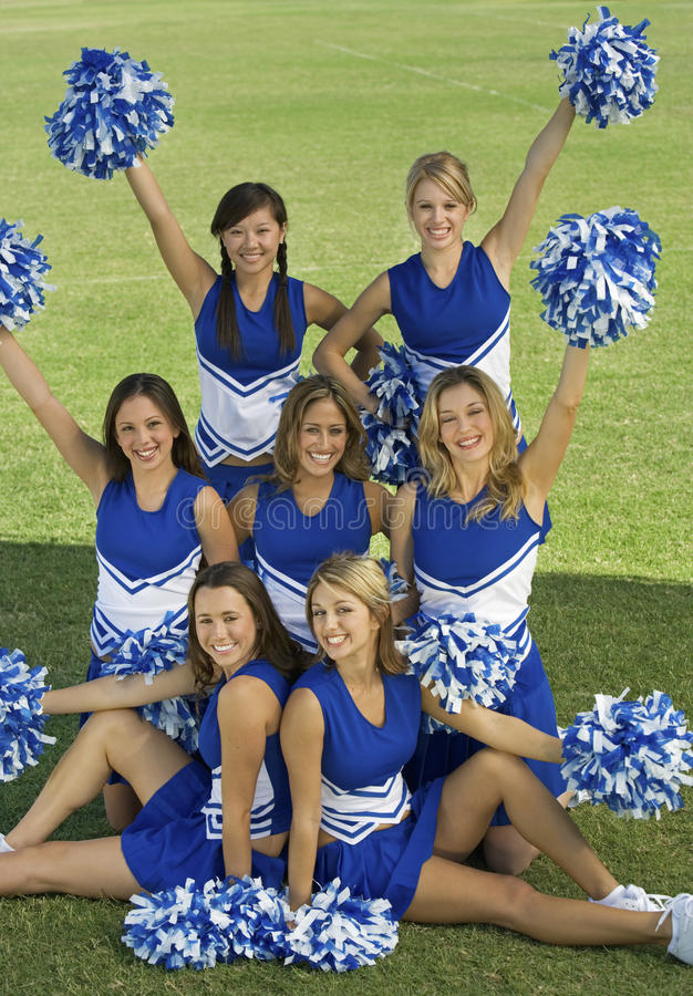 Cheerleaders Holding Pompoms On Field royalty free stock images
