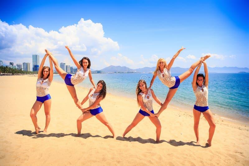 Cheerleaders perform double Heel Stretch on sand against sea. Cheerleaders in white blue uniform perform double Heel Stretch on sand beach smiles against sea stock images