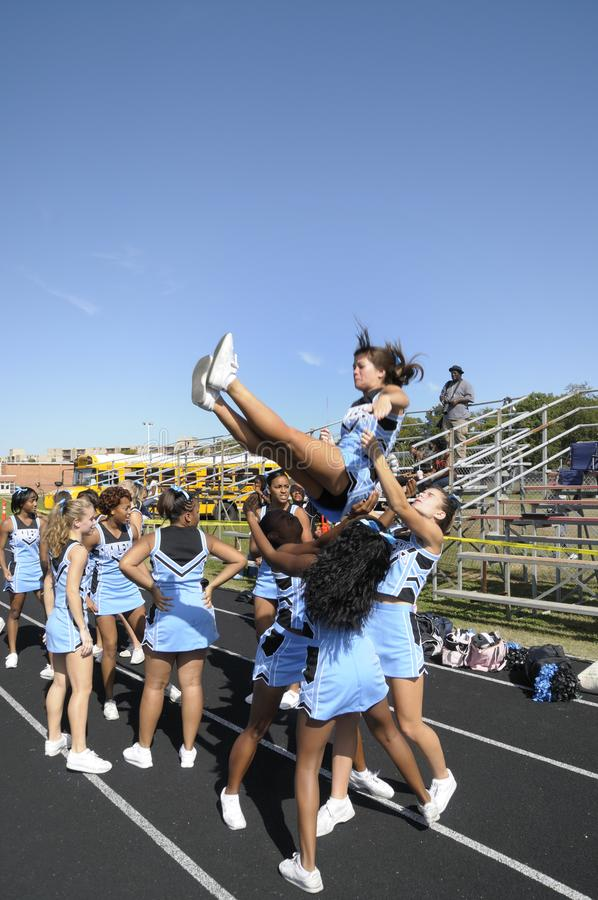 Cheerleaders perform at a football game in Greenbelt, Maryland. Cheerleaders perform different routines at a high school football game in Greenbelt, Maryland royalty free stock images