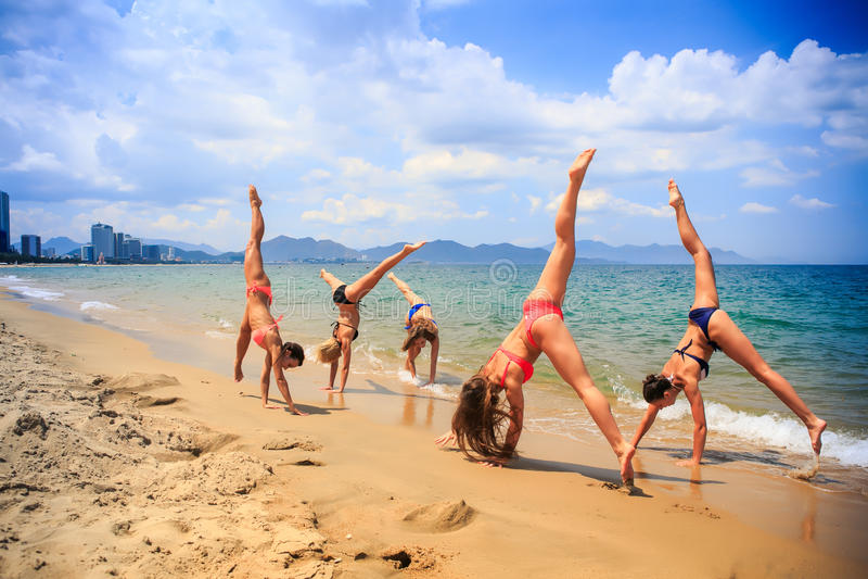 Cheerleaders perform hand scale and Heel Stretch on wet sand. Cheerleaders in colourful bikini perform hand scale and Heel Stretch on wet sand against azure sea stock photo
