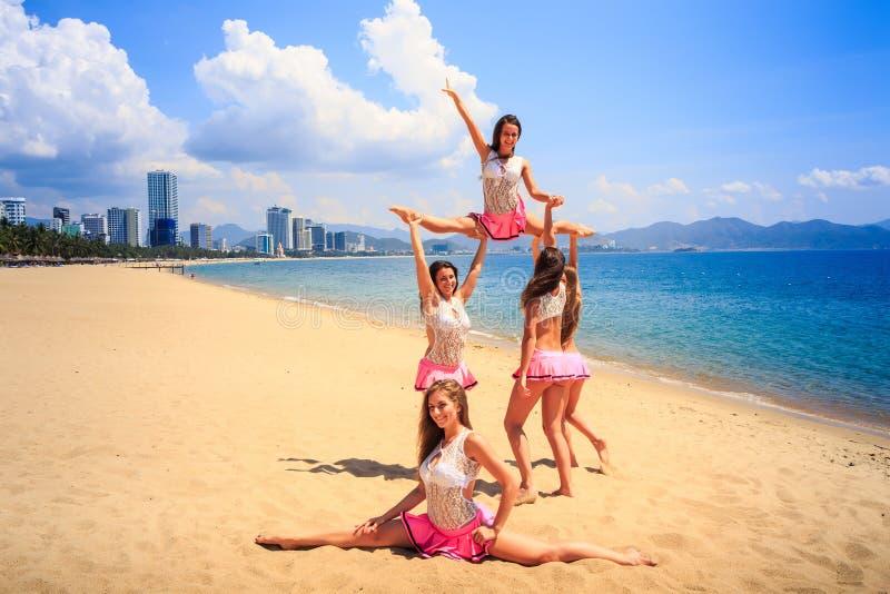 Cheerleaders perform High Straddle Stunt on beach against sea. Cheerleaders in white pink uniform perform High Straddle Stunt on sand beach against sea wind stock images
