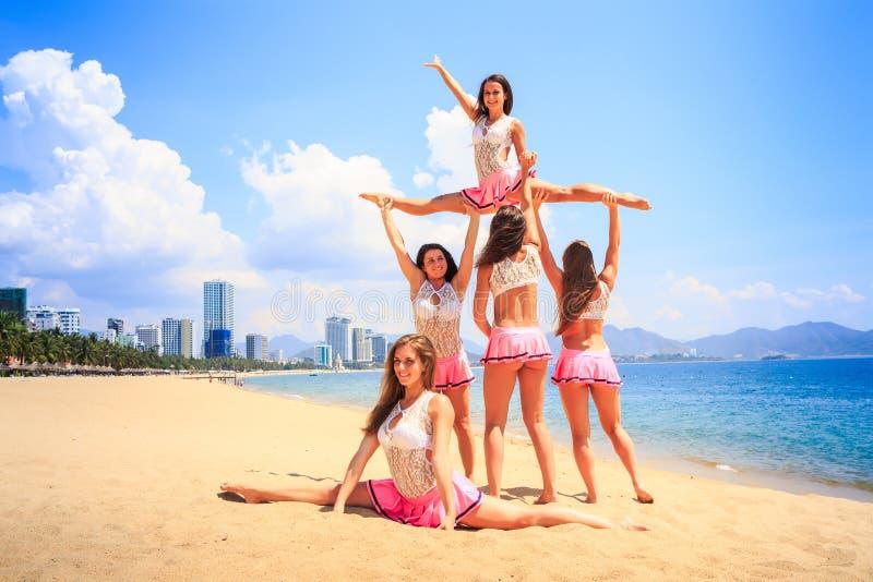 Cheerleaders perform High Straddle Stunt on beach against sea. Cheerleaders in white pink uniform perform High Straddle Stunt on sand beach against sea wind stock photos
