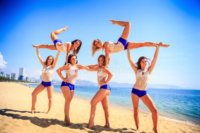 Cheerleaders perform sideview Swedish falls on beach against sea royalty free stock photos