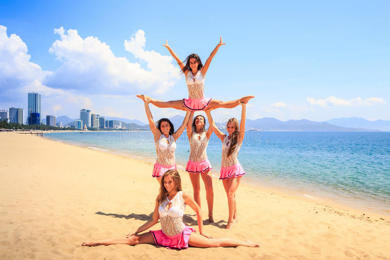 Cheerleaders perform Straddle Stunt with one split on beach. Cheerleaders in white pink uniform perform Straddle Stunt one girl does split on sand beach against royalty free stock photo