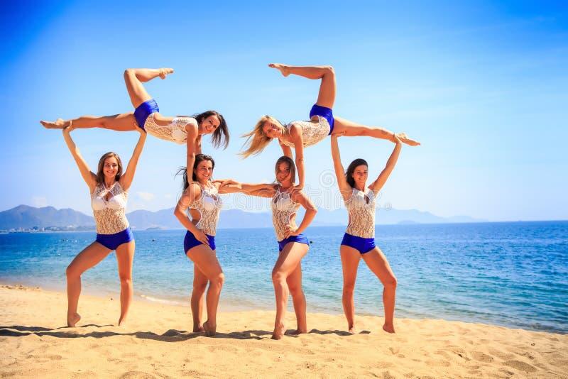 Cheerleaders perform Swedish falls on beach against azure sea stock photography