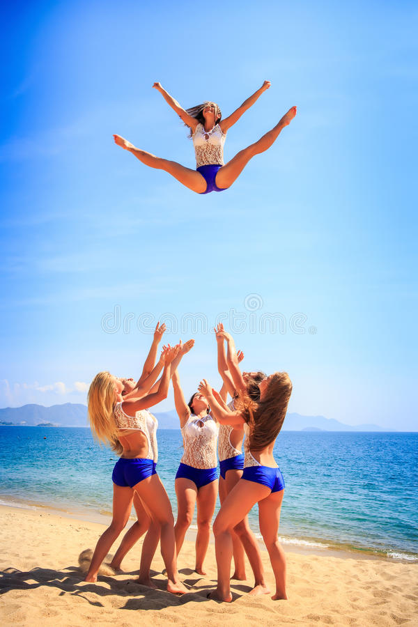 Cheerleaders perform Toe Touch Basket Toss on beach royalty free stock image