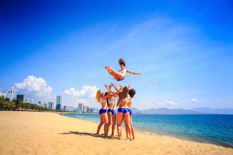 Cheerleaders perform tumbling toss on beach against azure sea royalty free stock photo