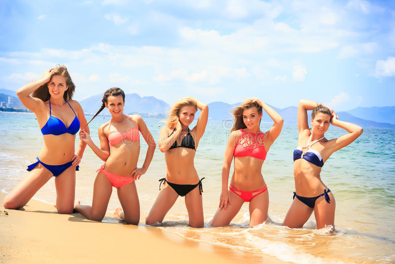 Cheerleaders pose in line hands upwards on beach against sea stock photos
