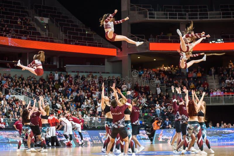 Cheerleaders skacze w powietrzu, podczas występu przy półetatowym balowej koszykówki latający gemowy obręcz obraz royalty free