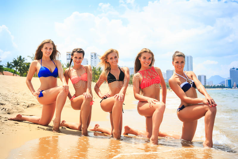 Cheerleaders stand in line on one knee on wet sand beach royalty free stock photos
