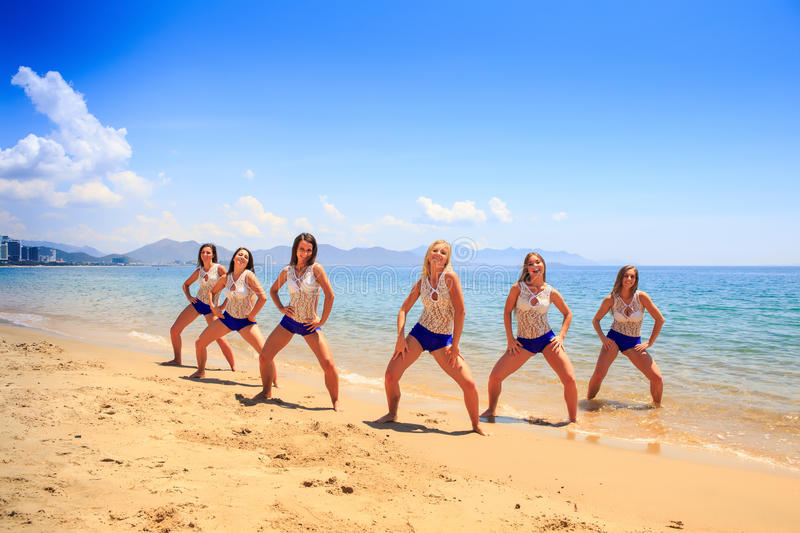 Cheerleaders stand in triangle pose hands on hips on wet sand stock images