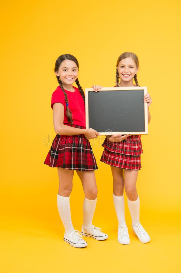 Cheerleading classes. School girls cute pupils red uniform hold blackboard copy space. School announcement concept stock photography