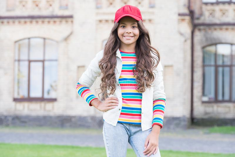 Cheerleading club. Cute child wear cap or snapback hat. Little girl wearing baseball cap. Girl long curly hair wear cap royalty free stock image