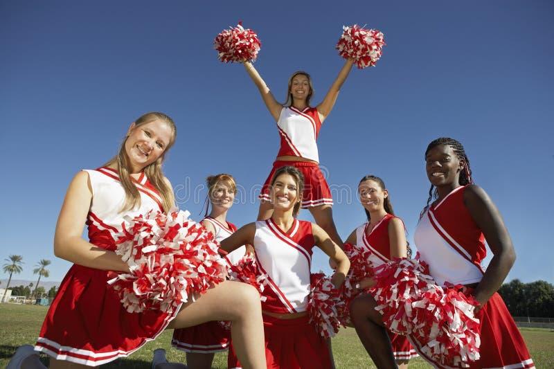 Cheerleading Gruppe in der Anordnung auf Feld lizenzfreies stockbild