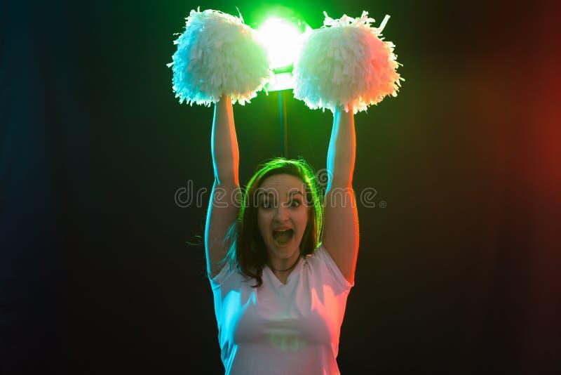 Cheerleading happy girl dancing on dark background royalty free stock images