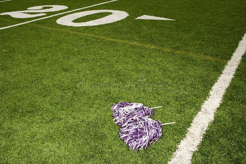 Cheerleading pom-poms på fotbollfält fotografering för bildbyråer